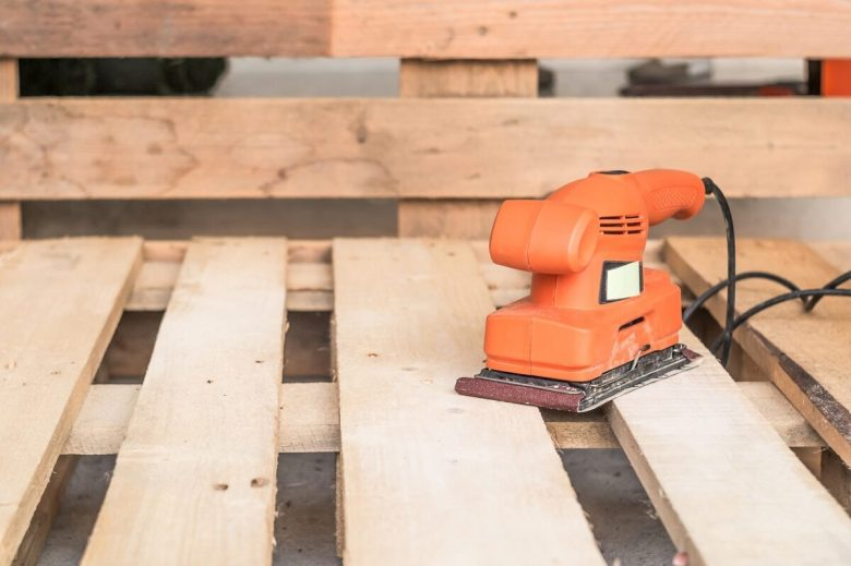 Wood sanding machines , Carpenter working with electrical sander on pine floor or table surface