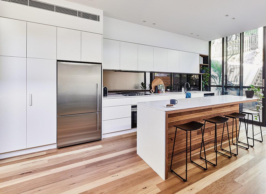 Große moderne Küche mit Holzboden, Kücheninsel und Fensterfront