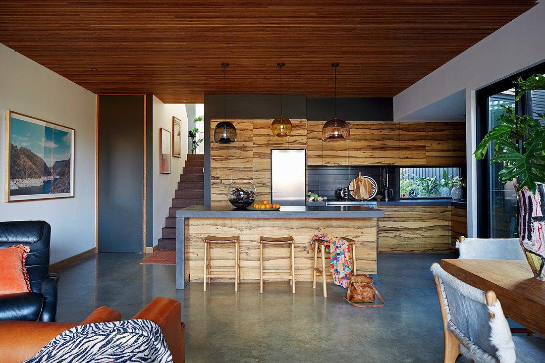 Küche mit Holzfronten in offenem Wohnraum mit Betonboden